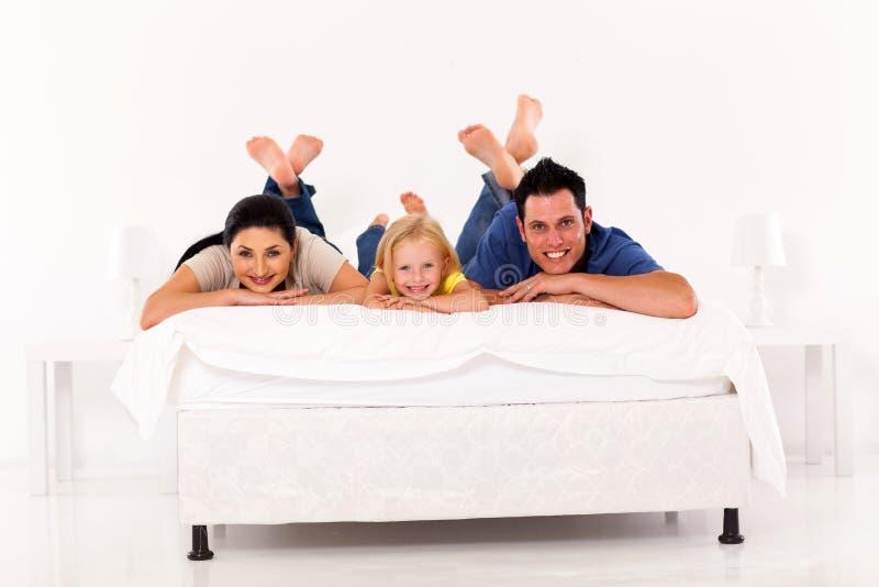 Familj på säng arkivbilder