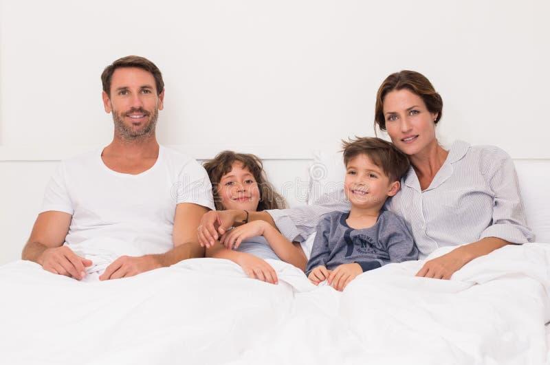 Familj på säng royaltyfri fotografi