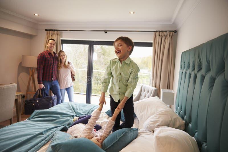 Familj på semester med barn som spelar på hotellsäng arkivfoto