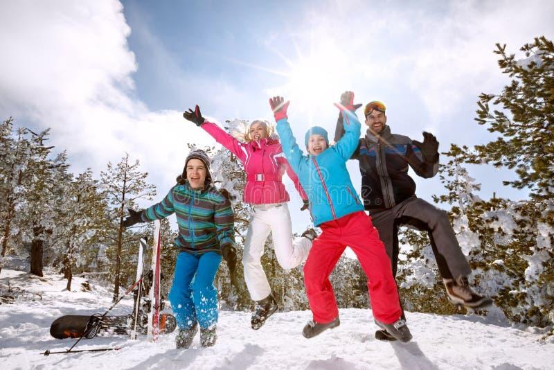 Familj på skidåkningbanhoppning på snö royaltyfri bild
