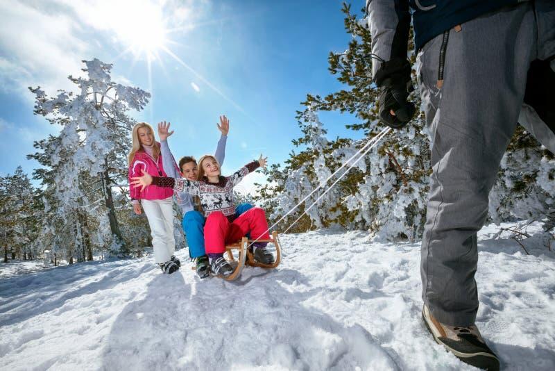Familj på snö som sledding och tycker om på solig vinterdag royaltyfri bild