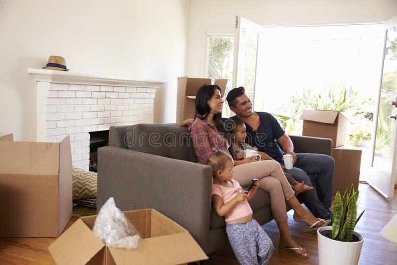 Familj på Sofa Taking ett avbrott från uppackning av hållande ögonen på TV royaltyfria foton