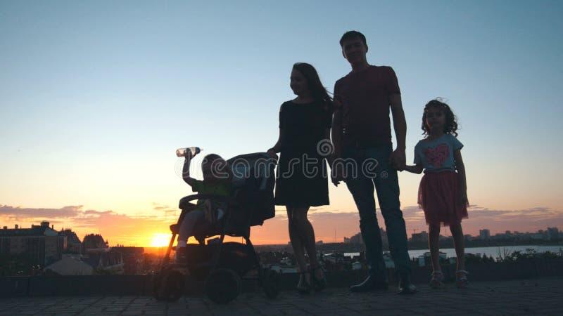 Familj på solnedgången - avla, fostra, dottern och den lilla sonen - kontur arkivbild