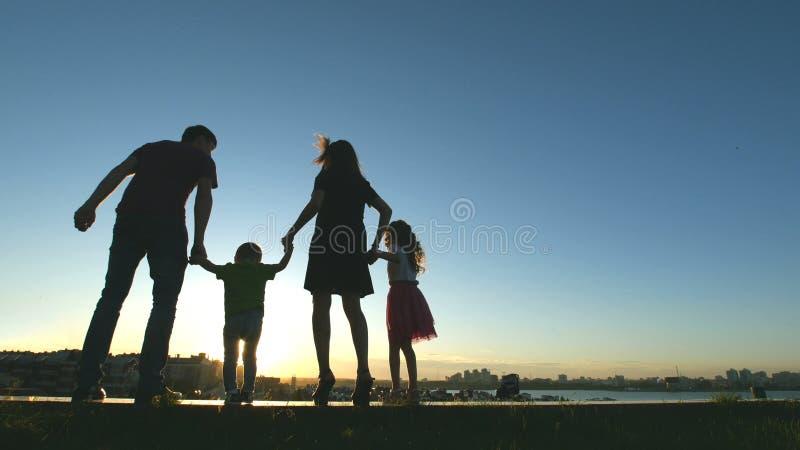 Familj på solnedgången - avla, fostra, dottern och den lilla sonen tillsammans - kontur arkivbilder