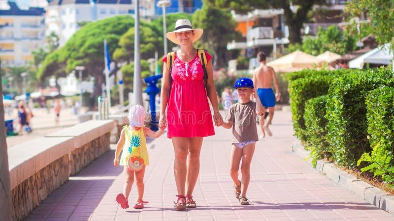 Familj på sommarsemestern som går till havsstranden royaltyfri bild