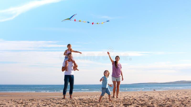 Familj på stranden med draken fotografering för bildbyråer
