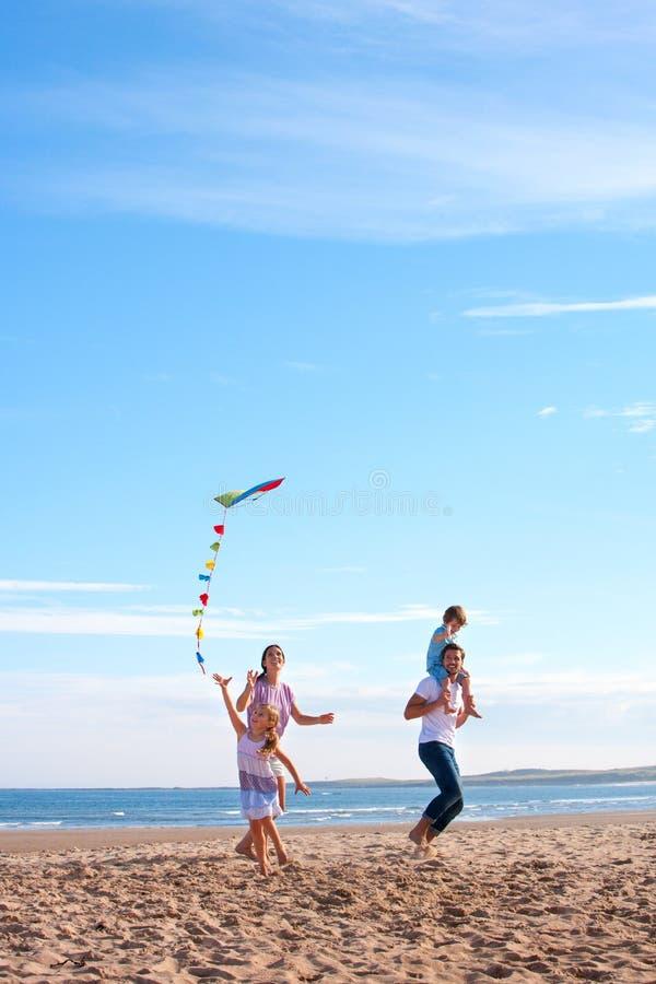 Familj på stranden med draken arkivbilder