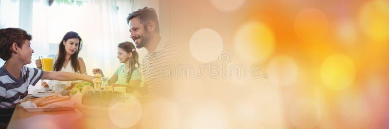 Familj på tabellen med orange bokehövergång fotografering för bildbyråer
