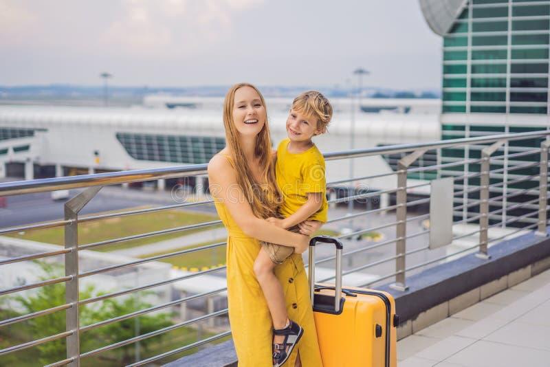 Familj p? flygplatsen f?r flyg Moder och son som väntar för att stiga ombord på avvikelseporten av den moderna internationella te fotografering för bildbyråer