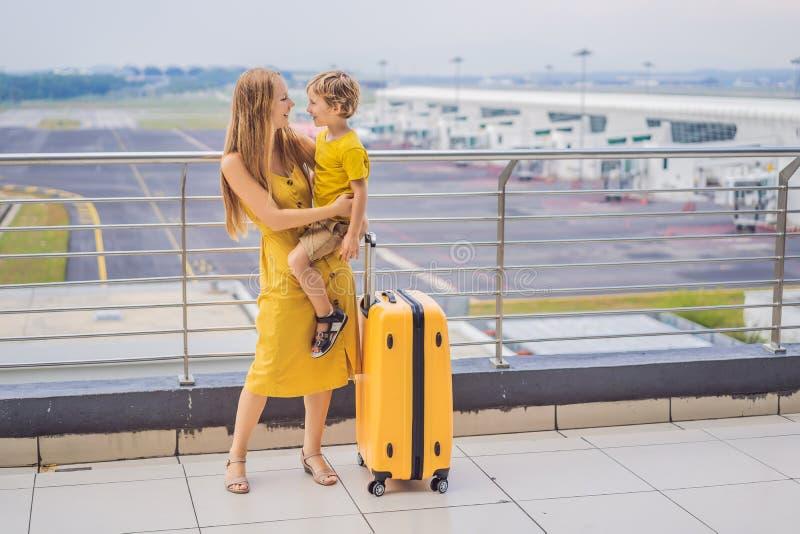 Familj p? flygplatsen f?r flyg Moder och son som väntar för att stiga ombord på avvikelseporten av den moderna internationella te arkivbild