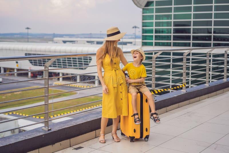 Familj p? flygplatsen f?r flyg Moder och son som väntar för att stiga ombord på avvikelseporten av den moderna internationella te royaltyfria foton