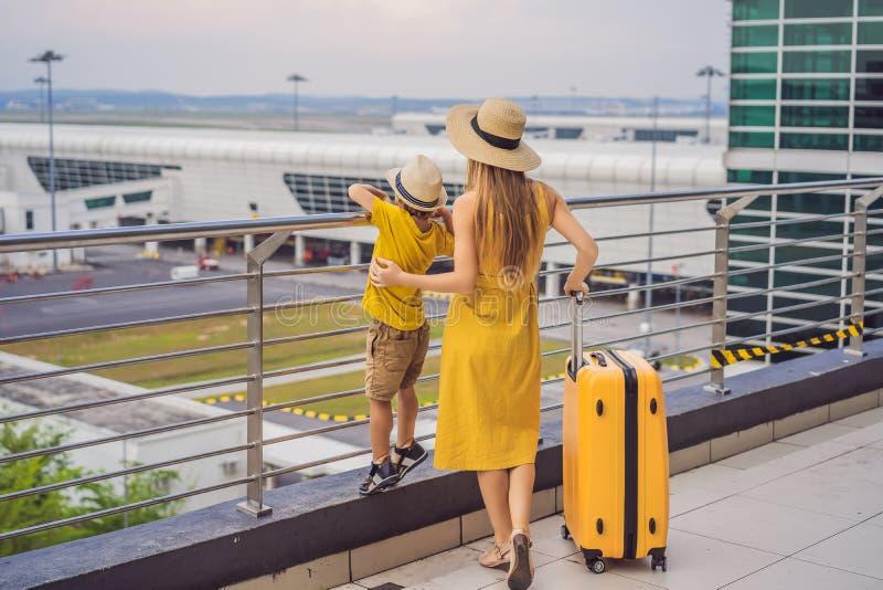 Familj p? flygplatsen f?r flyg Moder och son som väntar för att stiga ombord på avvikelseporten av den moderna internationella te royaltyfri bild