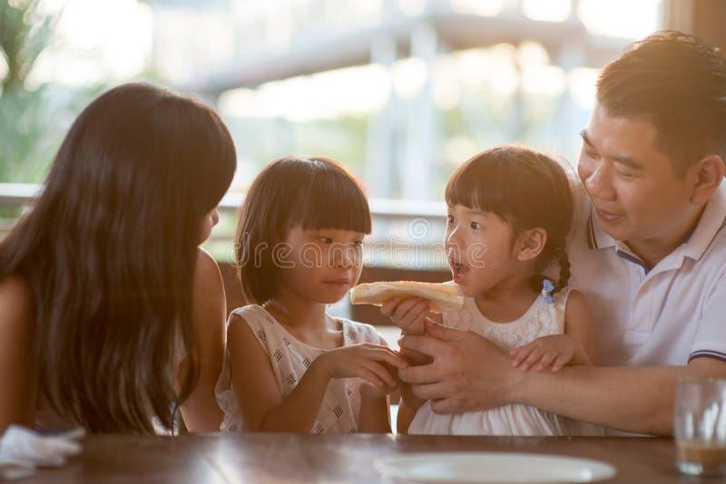 Familj som äter bröd på kafét arkivbilder