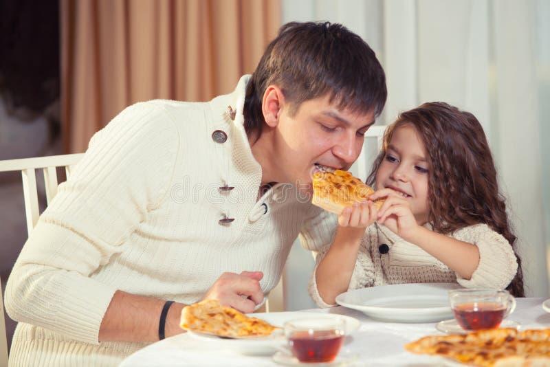 Familj som äter matställen på en äta middag tabell, rund tabell, pizza, apelsin, hus som göras av trä royaltyfri fotografi