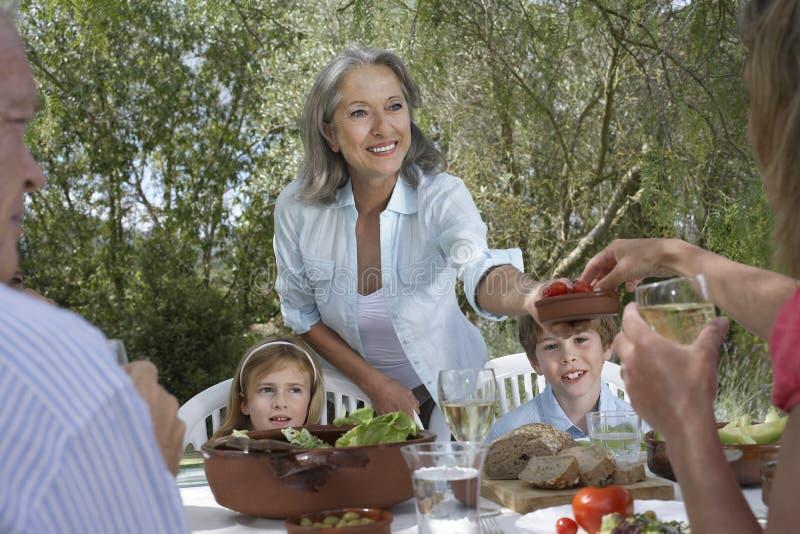 Familj som äter på den trädgårds- tabellen royaltyfri foto