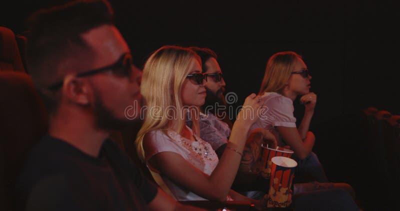 Familj som äter popcorn i bio arkivfoto