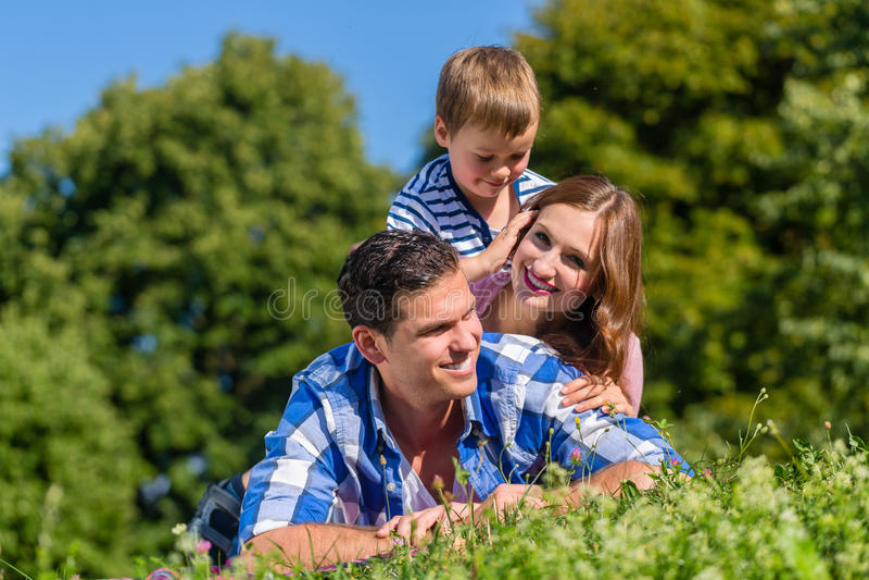 Familj som överst ligger i gräs av de royaltyfria foton
