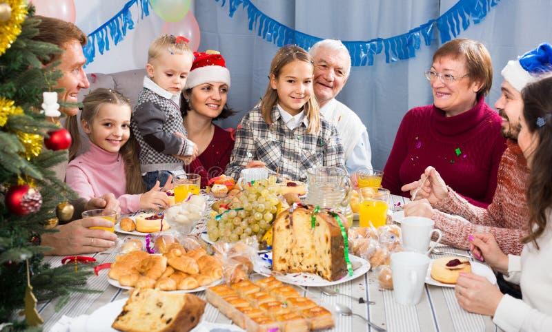 Familj som animatedly talar under julmatställe fotografering för bildbyråer