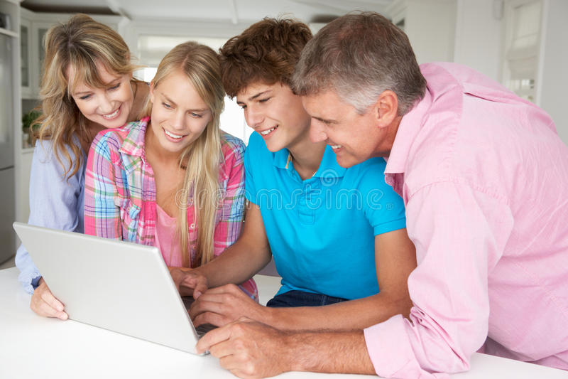 Familj som använder bärbar dator på tabellen royaltyfria foton