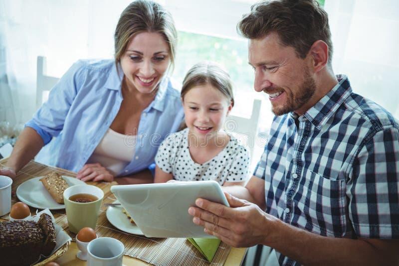 Familj som använder den digitala minnestavlan, medan ha frukosten arkivbild
