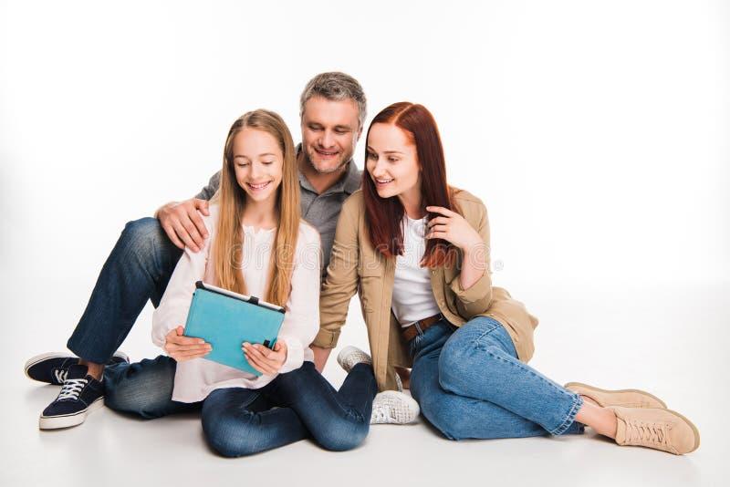 Familj som använder den digitala tableten royaltyfri bild