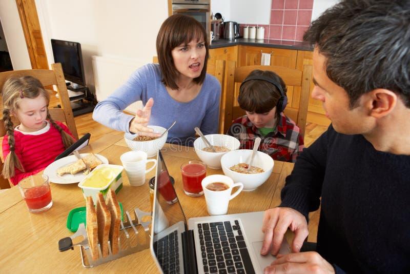Familj som använder grejstunden som äter frukosten royaltyfri foto