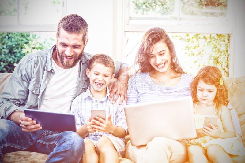 Familj som använder teknologier, medan sitta på soffan arkivfoto