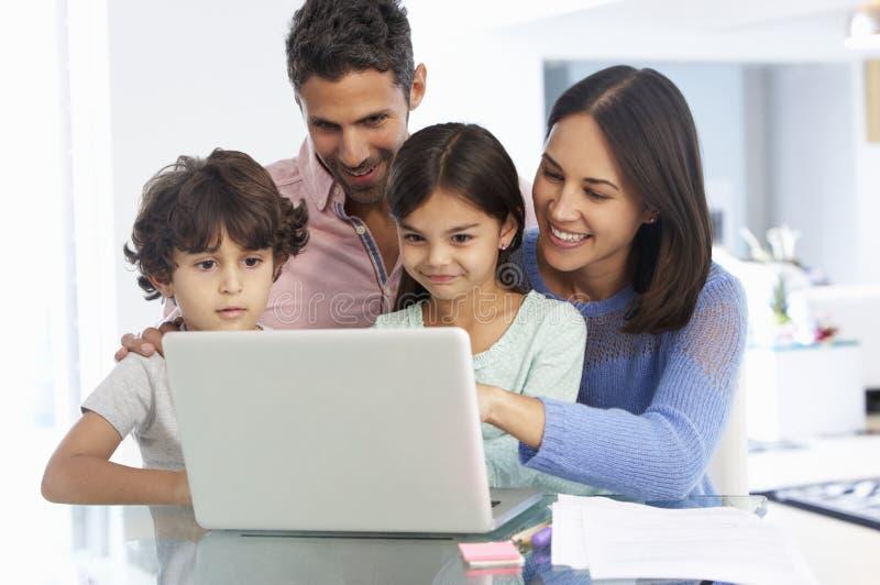 Familj som arbetar på bärbara datorn med i inrikesdepartementet royaltyfri fotografi