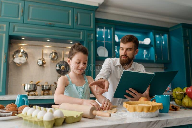 Familj som bakar bakelser i kök arkivfoto
