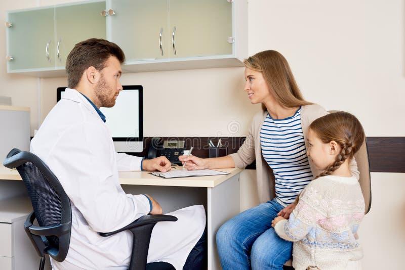 Familj som besöker doktorn royaltyfri fotografi