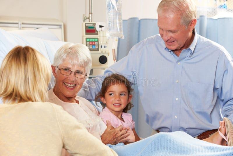 Familj som besöker hög kvinnlig tålmodig i sjukhussäng royaltyfri foto