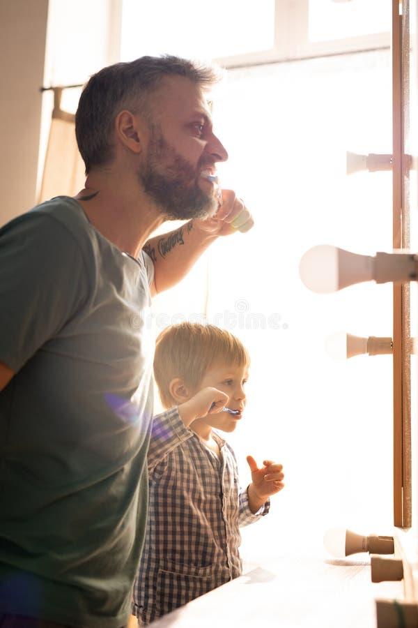 Familj som borstar tänder i badrum arkivbilder