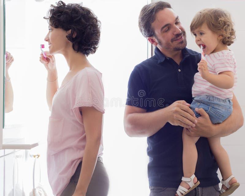 Familj som borstar tänder i badrumspegel royaltyfria bilder