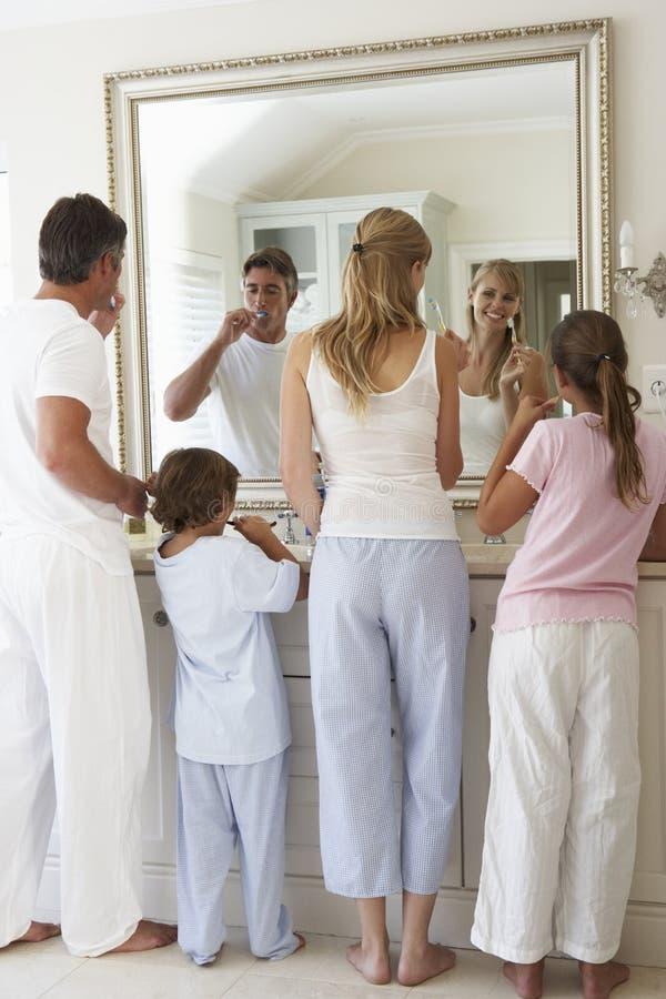 Familj som borstar tänder i badrumspegel arkivbild