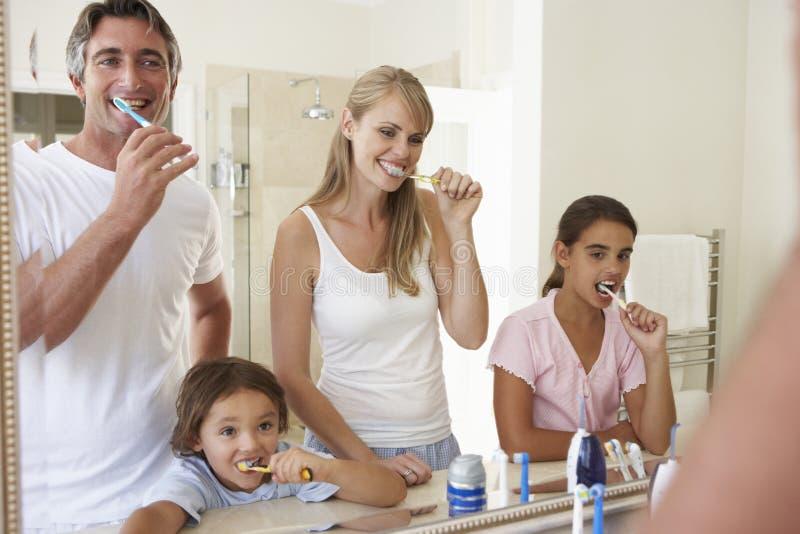 Familj som borstar tänder i badrumspegel royaltyfria foton