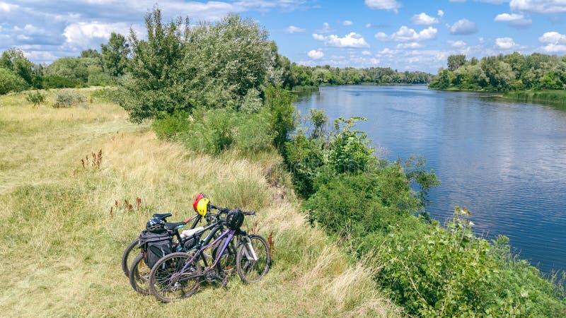 Familj som cyklar det fria, cyklar nära floden, flyg- sikt av cyklar och hjälmar från ovannämnt, sport och kondition royaltyfri bild