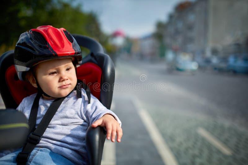 Familj som cyklar i staden Bärande hjälmar för liten härlig flicka i cykelplats royaltyfri foto