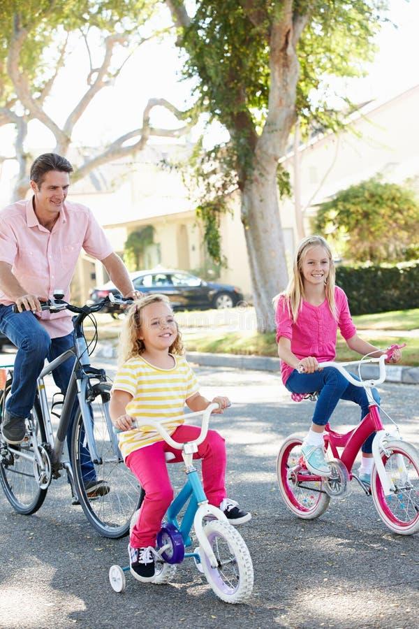 Familj som cyklar på den förorts- gatan royaltyfri fotografi