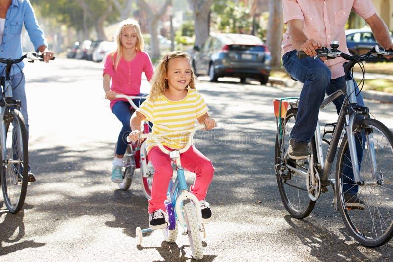Familj som cyklar på den förorts- gatan arkivbilder