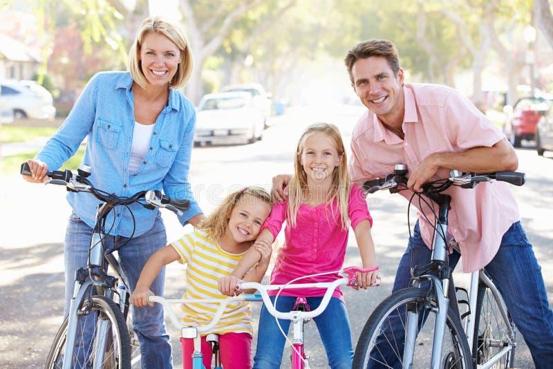 Familj som cyklar på den förorts- gatan fotografering för bildbyråer