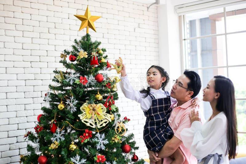 Familj som dekorerar en julgran och en fader som ger julG fotografering för bildbyråer
