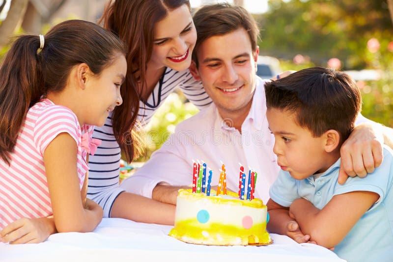 Familj som firar födelsedag utomhus med kakan arkivfoto