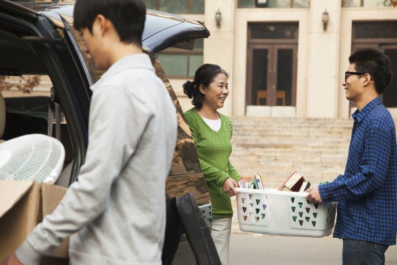 Familj som flyttar deras son in i sovsal på högskolauniversitetsområde arkivfoton