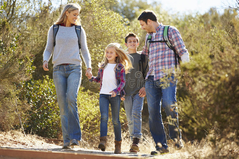 Familj som fotvandrar i bärande ryggsäckar för bygd royaltyfri foto