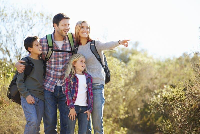 Familj som fotvandrar i bärande ryggsäckar för bygd royaltyfria bilder