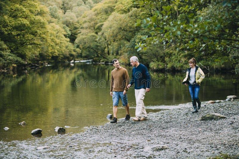 Familj som fotvandrar rundan sjöområdet fotografering för bildbyråer