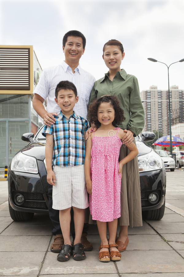 Familj som framme ler och står av bilen, stående royaltyfri bild