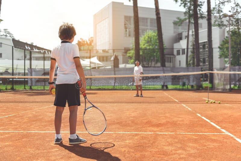 Familj som går att spela tennis royaltyfria bilder