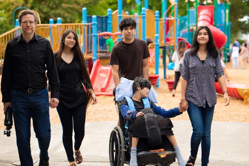 Familj som går förbi lekplats med den rörelsehindrade sonen i rullstol arkivfoton