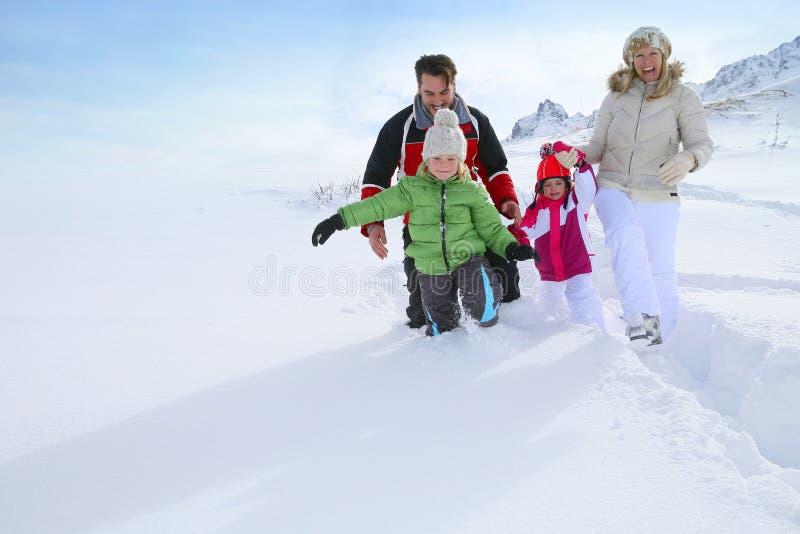 Familj som går i ny snö arkivbilder